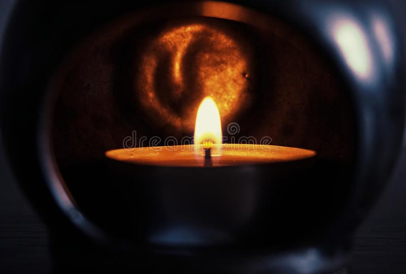 Brännande stearinljus i ett mörkt ställe royaltyfria bilder