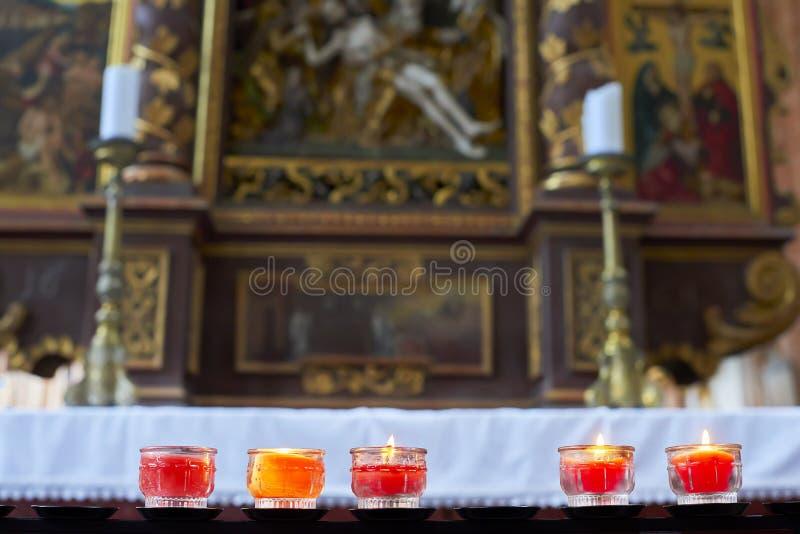 Brännande stearinljus i färgrika stearinljushållare i en kyrka arkivfoton