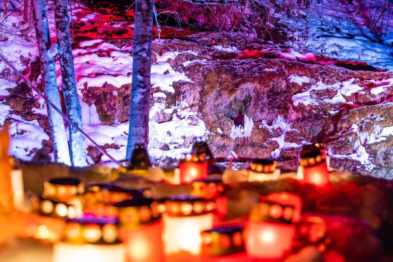 Brännande stearinljus i gula och röda färger med grunt djup av fältet med röd bakgrund och utrymme för text - 02 02 händelse 2019 arkivbilder