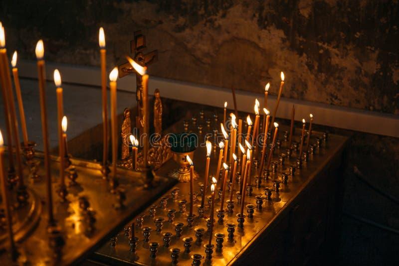Brännande stearinljus i kyrka eller tempel arkivfoto