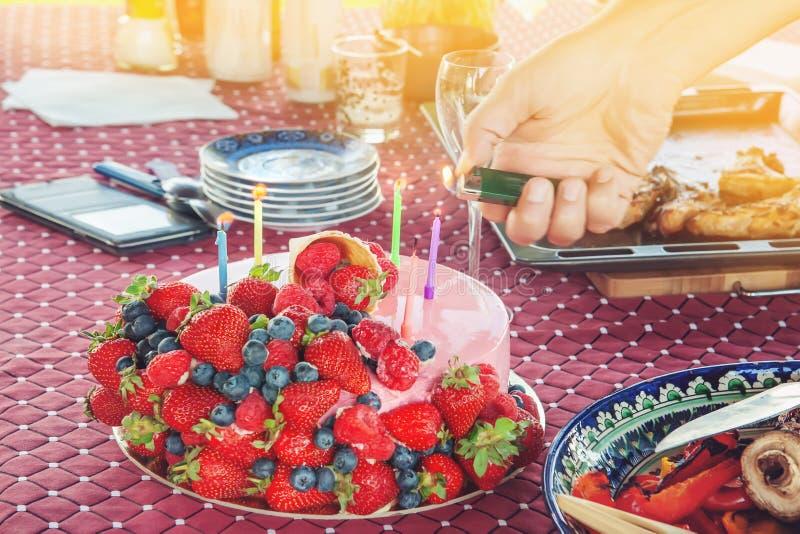 Brännande stearinljus på en kaka med olika bär på barns parti Jordgubbar och blåbär för en läcker efterrätt royaltyfria foton