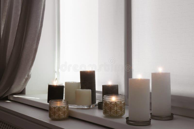 Brännande stearinljus på fönsterfönsterbräda arkivfoto