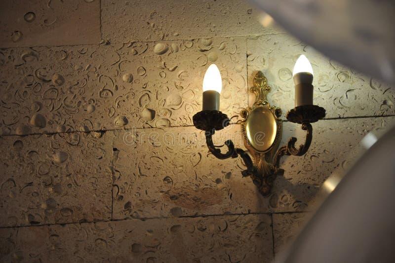 Brännande stearinljus på stenväggen i gammal slott ljust värme garnering royaltyfria bilder