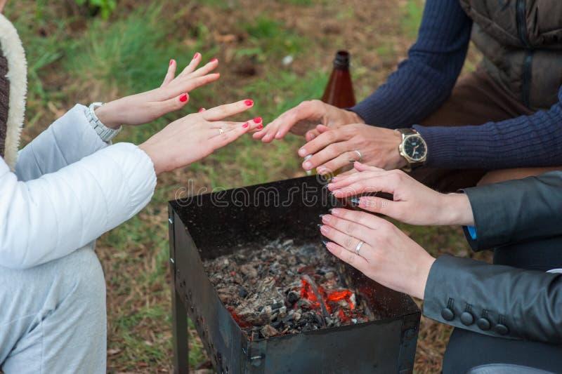 Brännande trä i gallret och röda kol med strömmen som kommer upp från den Pysen i rött lag värme hans djupfrysta händer över arkivbild