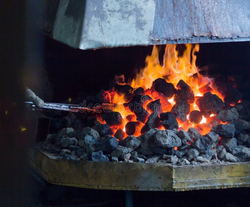 Brännhet panna med kol och varma metalldelar för vidareförädling, gammal smedja, kol royaltyfria foton