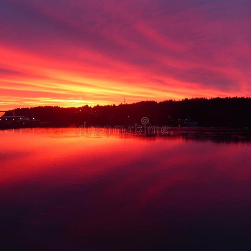 Brännhet röd och orange solnedgång över Stillahavs- öppning in i inre av Alaska royaltyfri bild