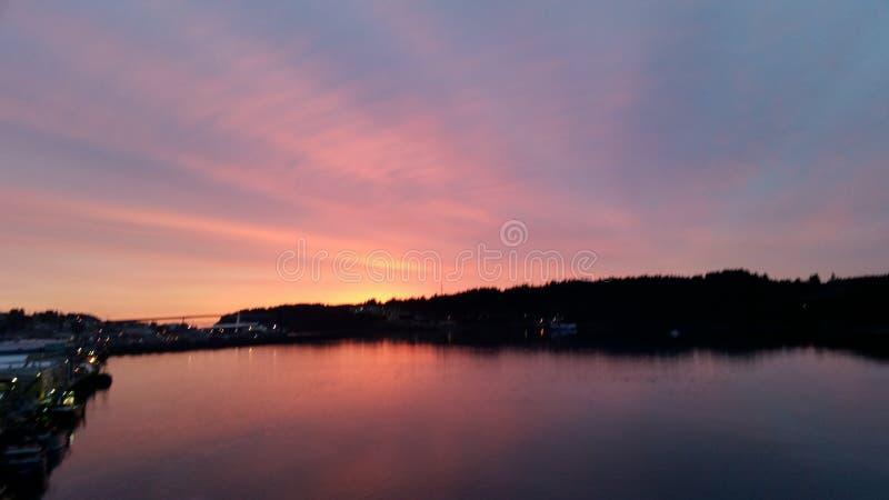 Brännhet röd och orange solnedgång över Stillahavs- öppning in i inre av Alaska royaltyfri foto