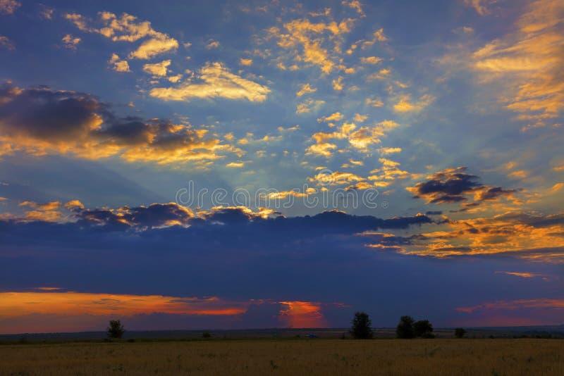 Brännhet rödaktig solnedgång över ett fält i ett lantligt aftonlandskap arkivbilder
