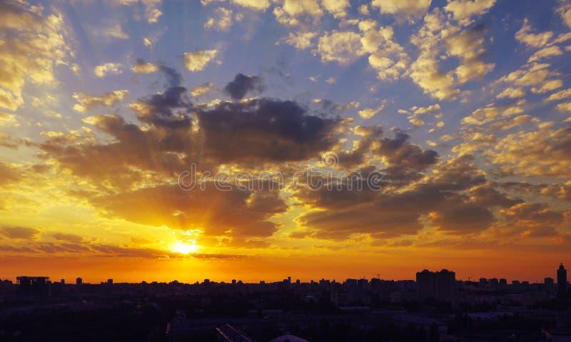 Brännhet rödaktig soluppgång över en sova stad arkivbilder
