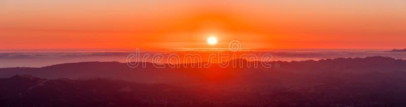 Brännhet solnedgång över ett hav av moln fotografering för bildbyråer