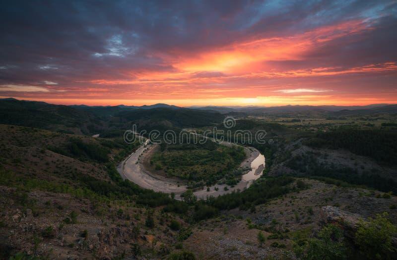 Brännhet solnedgång över flodkrökningen i bergen royaltyfria bilder