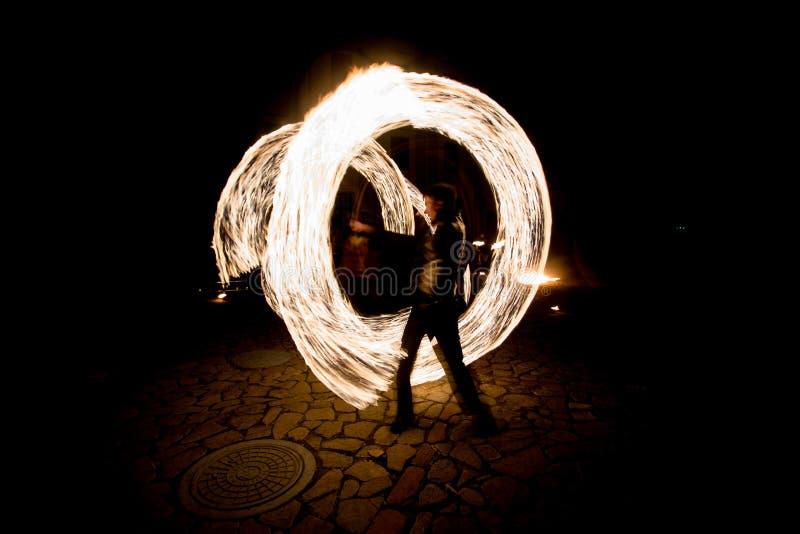 Brännheta strimmor under fireshowen på natten arkivfoto