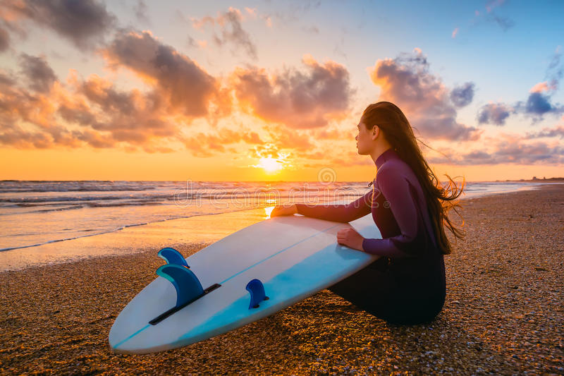 Bränningflicka och hav Härlig surfareflicka för ung kvinna med surfingbrädan på en strand på solnedgången eller soluppgång arkivfoto