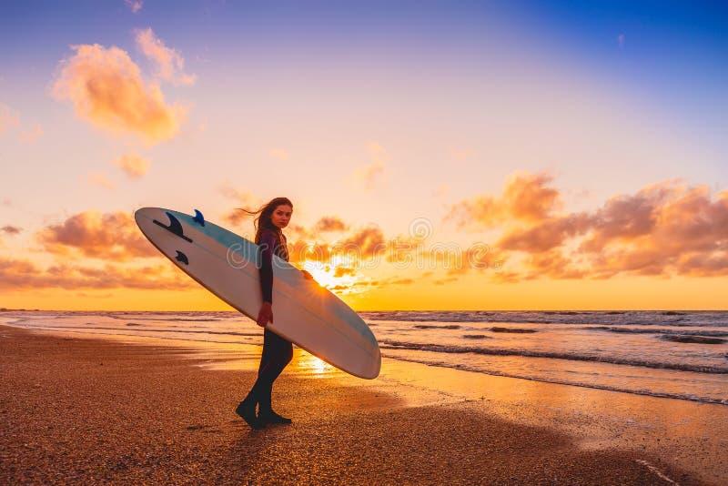 Bränningflickan med longboard går till att surfa Kvinna med surfingbrädan på en strand på solnedgången arkivfoto