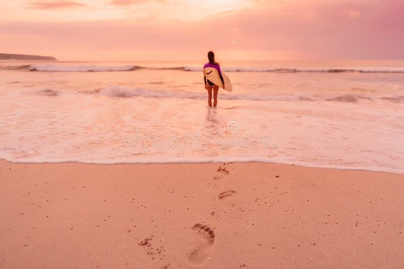 Bränningflickan med surfingbrädan går till att surfa Surfarekvinna på en strand på solnedgången eller soluppgång royaltyfria bilder
