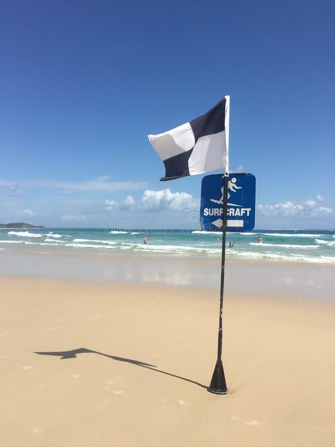 Bränninghantverkflaggor på en australisk strand royaltyfri foto