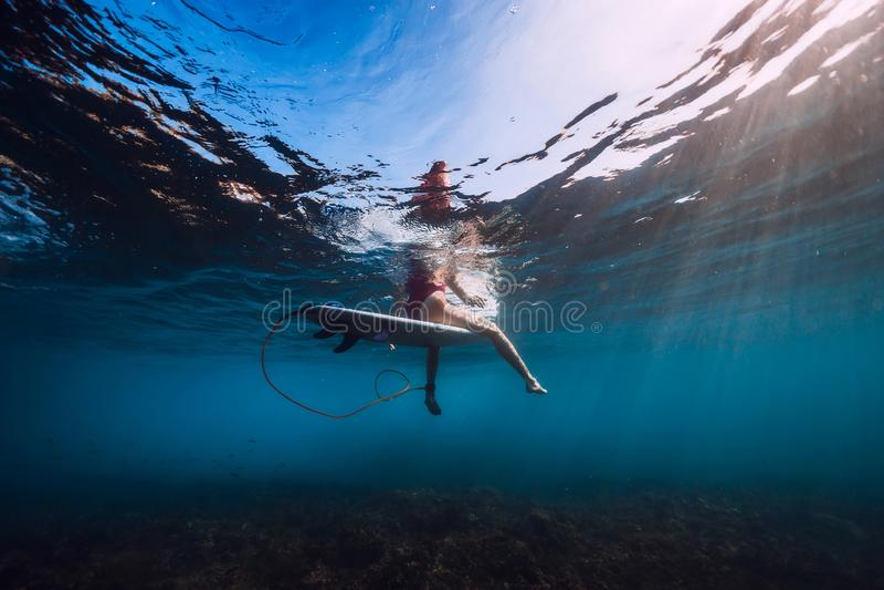 Bränningkvinnan sitter på surfingbrädan, undervattens- sikt av surfaren i havet arkivbilder