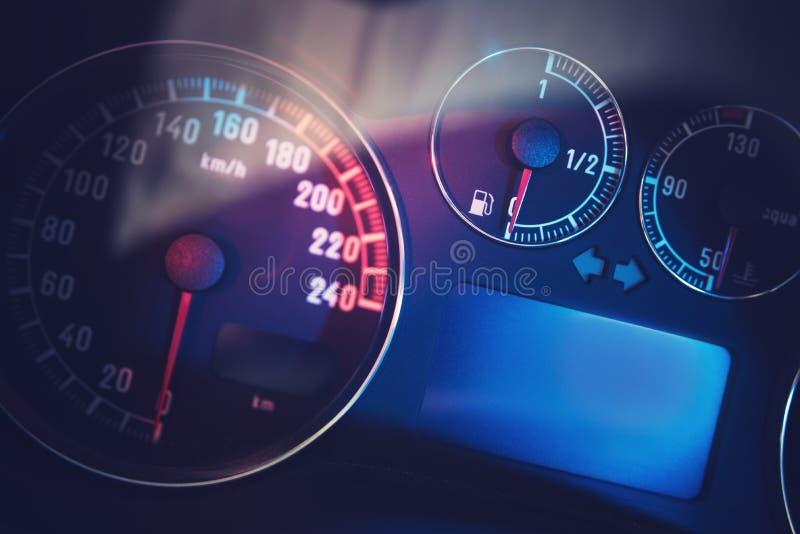 Bränslemått och bilhastighetsmätare med röda och blåa ljus arkivbilder
