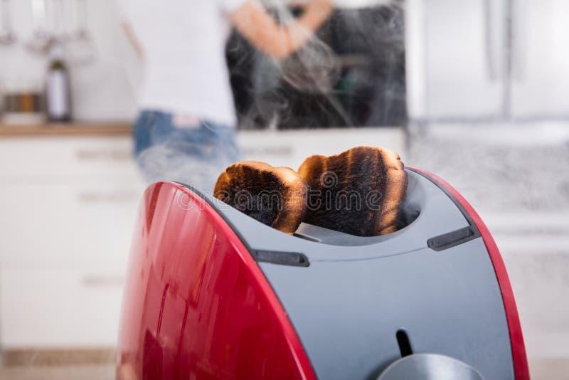 Bränt rostat bröd som kommer ut ur brödrosten royaltyfri fotografi