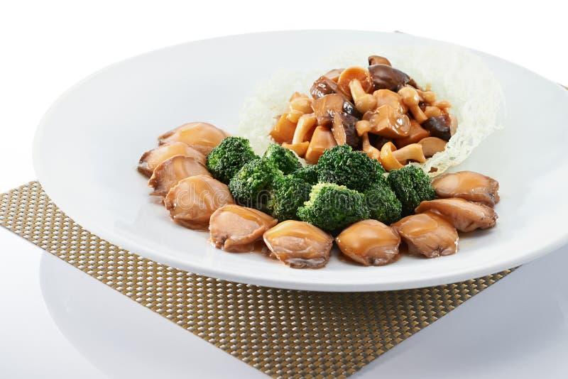 Bräserad abalone med broccoli med det guld- underlägget royaltyfria bilder