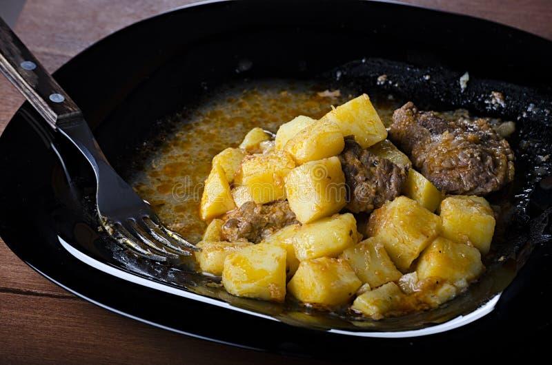 Bräserade potatisar med kött och sky på en svart platta, sikt för closeup 45 royaltyfri fotografi