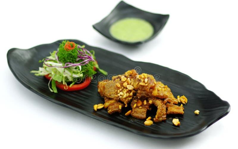 Bräserat griskött med chilisås och sallad på det svarta uppläggningsfatet royaltyfri bild