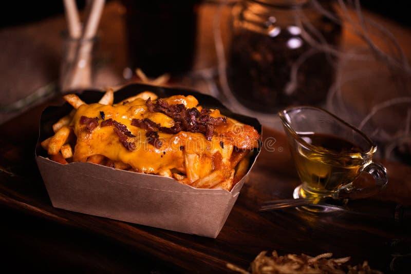 Brät Lebensmittelfoto Straßenlebensmittel Ungesunde geschmackvolle gegrillte Pommes-Frites mit Käse und Speck im selbst gemachten lizenzfreies stockfoto