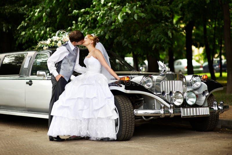 Bräutigam-ADN-Braut über Retro- Limousine lizenzfreie stockfotografie