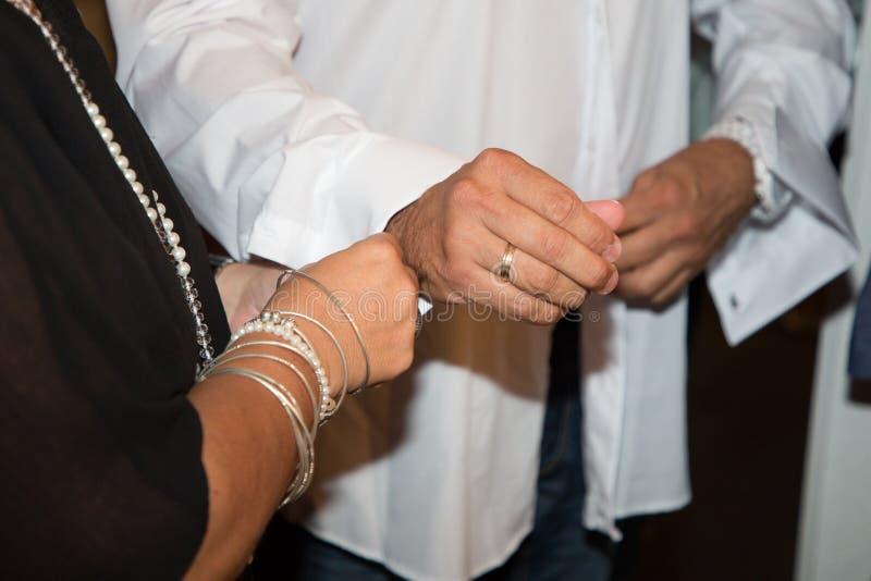 Bräutigam bereitet vor sich, indem er seine Manschettenknöpfe am Tag der Hochzeit setzt stockfotos