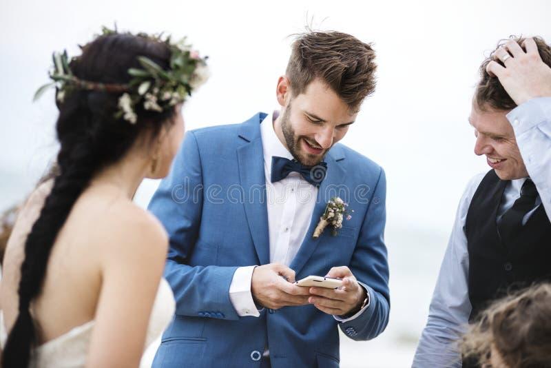 Bräutigam besetzt mit Telefon an der Strandhochzeitszeremonie lizenzfreies stockbild