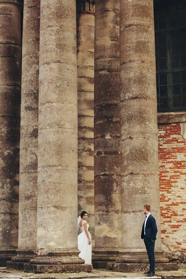 Bräutigam betrachtet Braut, die zwischen den Säulen steht stockfoto