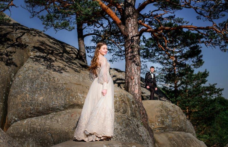 Bräutigam betrachtet die schöne Braut, die auf den Felsen steht lizenzfreie stockfotos