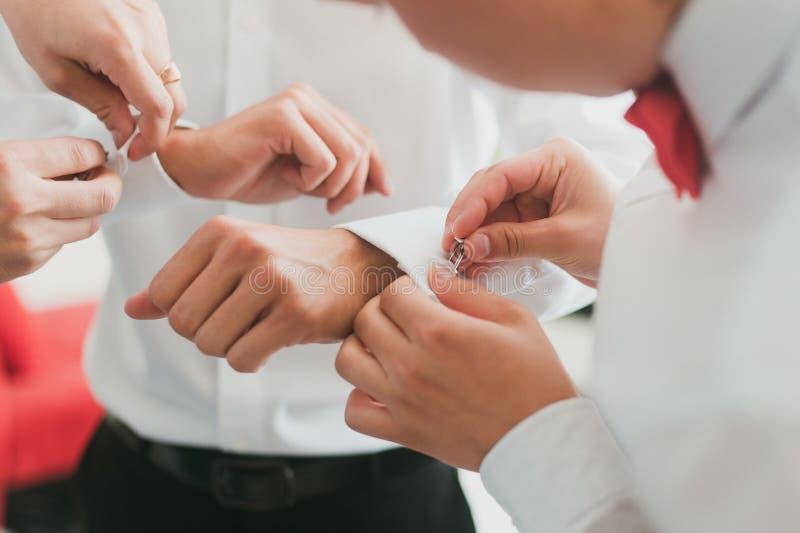 Bräutigam, der auf seine Manschettenknöpfe sich setzt lizenzfreie stockfotografie
