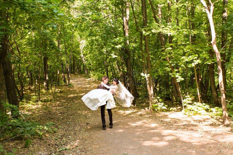 Bräutigam, der Braut in seinen Armen hält lizenzfreie stockfotografie