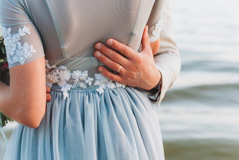 Bräutigam, der seine Hand auf der Taille seiner Braut, stehend auf einem Strand hat stockbild