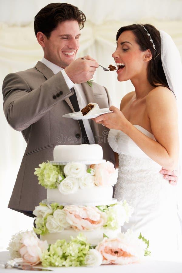 Bräutigam-Feeding Bride With-Hochzeitstorte an der Aufnahme lizenzfreie stockfotografie