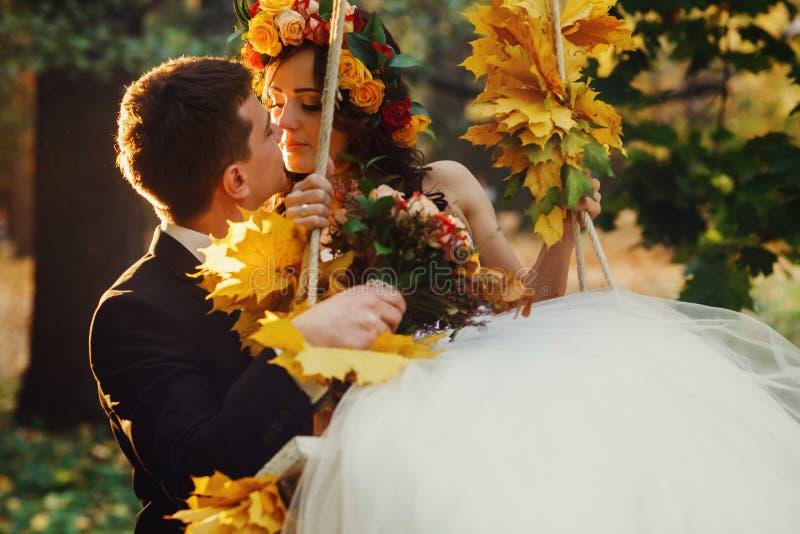 Bräutigam hält eine Braut in einem Schwingen, das mit gelbem gefallenem leav verziert wird lizenzfreie stockfotografie