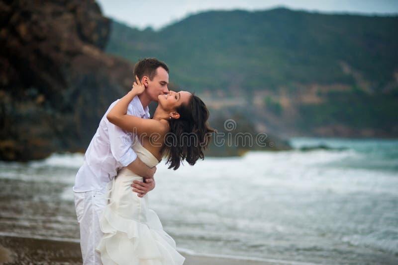 Bräutigam küsst die Braut in dem Meer Paare in der Liebe auf einem einsamen Strand stockfotos