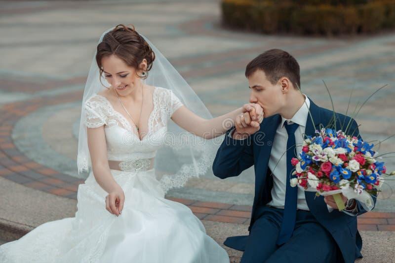Bräutigam küsst die Hand der Braut stockbild