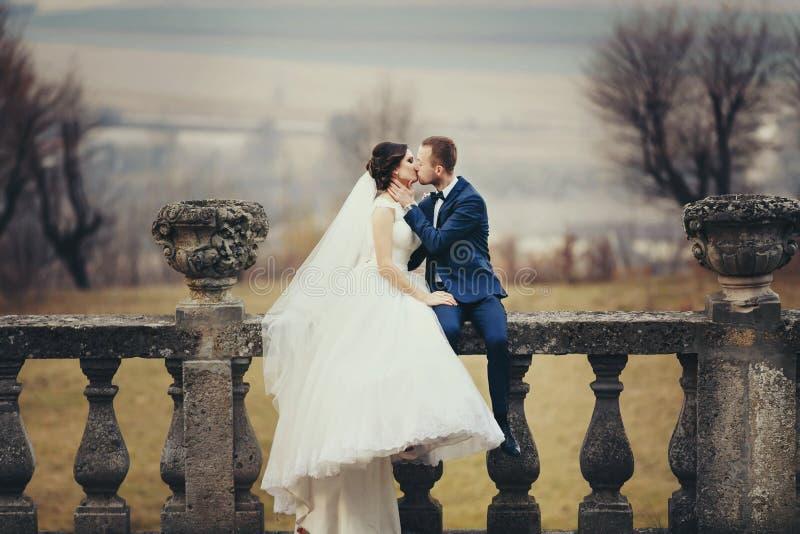 Bräutigam küsst eine Braut, die mit ihr auf dem Balkon mit einem grea sitzt stockbilder