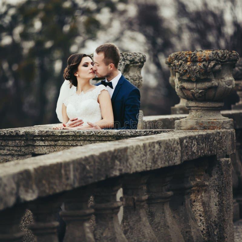 Bräutigam küsst eine Braut, die sie von hinten auf dem alten Balkon umarmt lizenzfreie stockfotografie