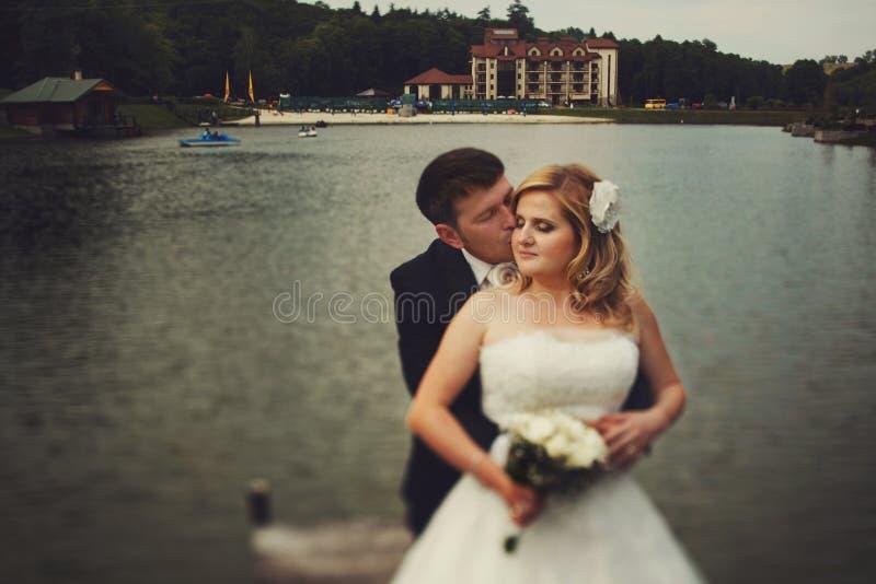 Bräutigam küsst eine Braut, die sie von hinten bei der Stellung auf t umarmt stockbild