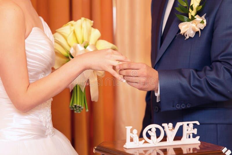 Bräutigam kleidet einen Ring auf Finger zur Braut stockfotografie