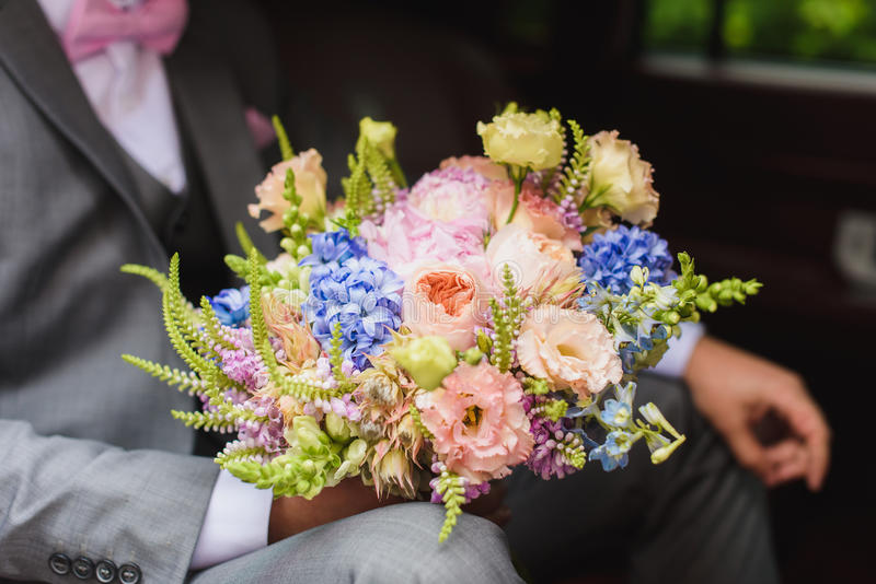 Bräutigam mit Blumenstrauß im Hochzeitsauto stockbilder