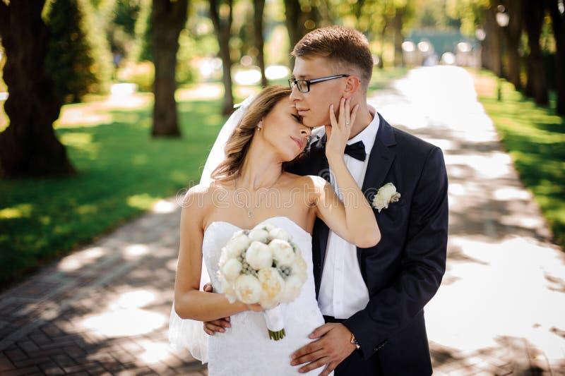 Bräutigam mit Gläsern und Braut mit einem Blumenstrauß von Pfingstrosen umarmen leicht im Park stockbild