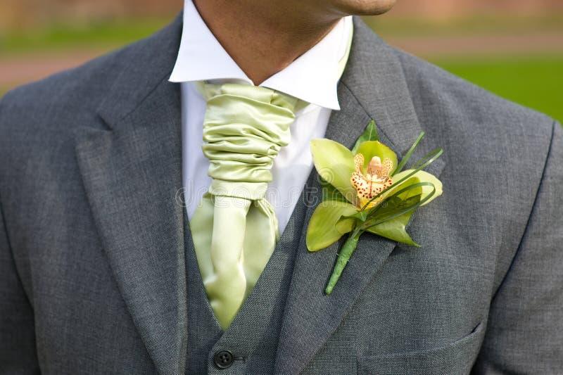 Bräutigam mit Orchideeknopfloch an der Hochzeit stockfotos
