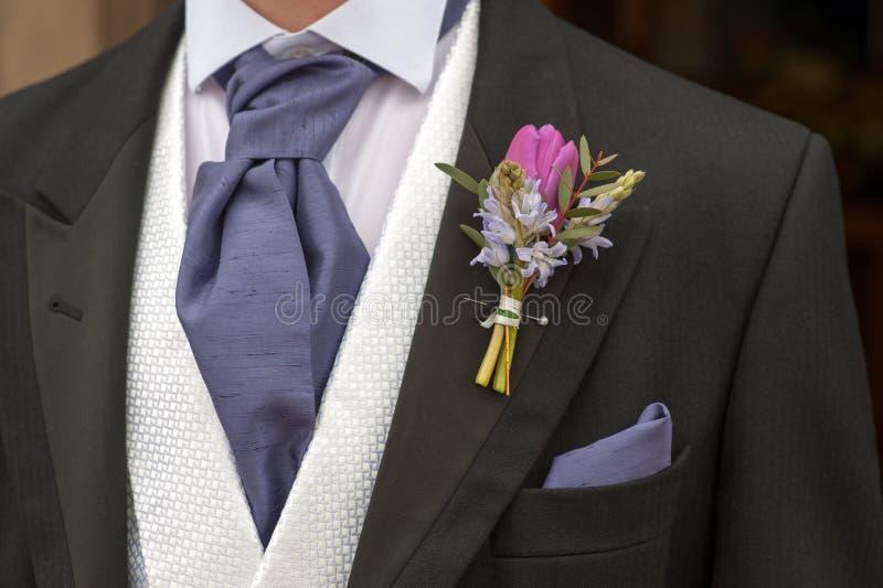 Bräutigam mit purpurrotem Blumenknopfloch stockfoto