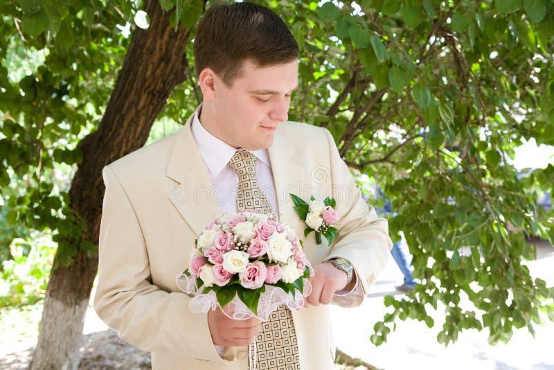 Bräutigam mit Uhr stockbild