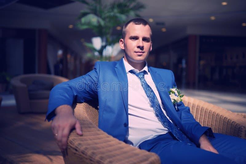Bräutigam sitzen auf dem Stuhl im Café lizenzfreie stockfotos