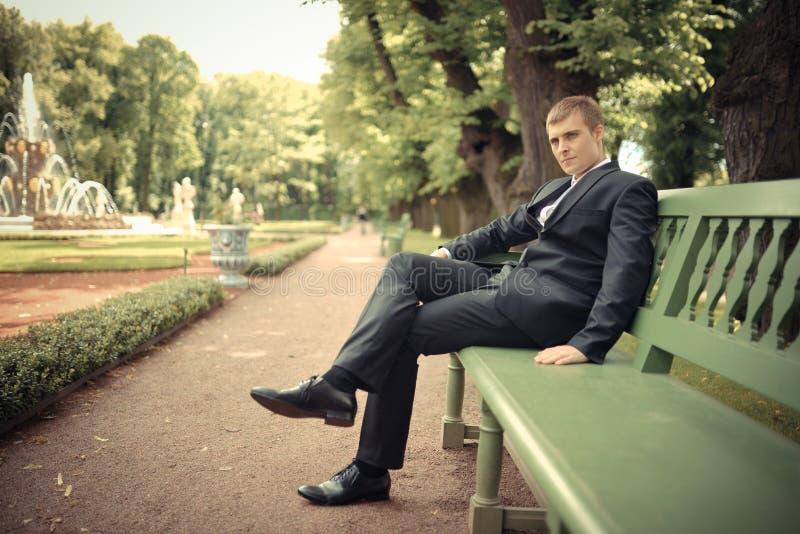 Bräutigam sitzen auf der Bank in einem Park lizenzfreie stockfotografie